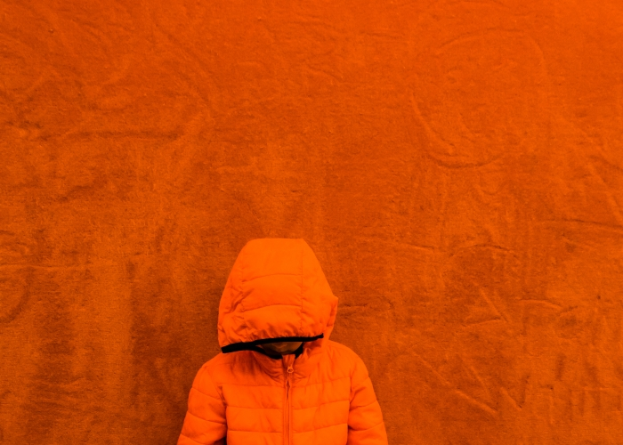 Orange jacket boy in front of orange wall diana hagues photograp