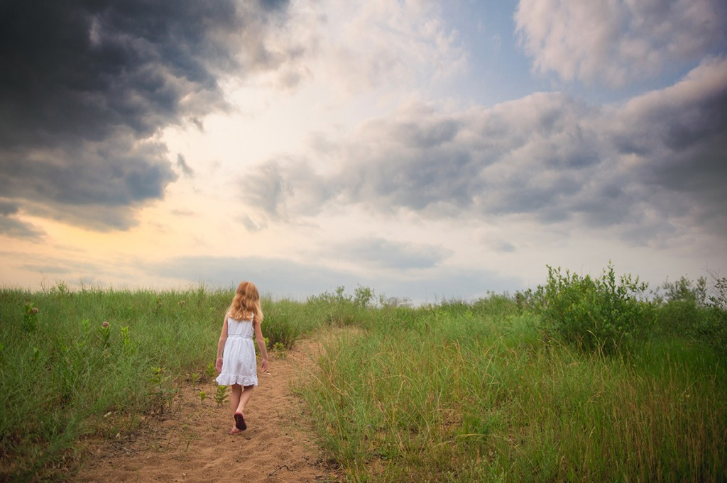 picture of a girl walking in a field by Mickie DeVries