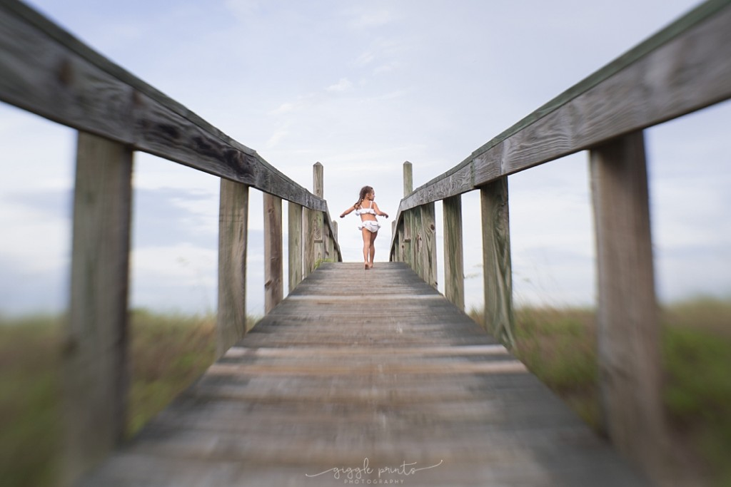 Lensbaby picture of girl running on a pier by Marcie Reif