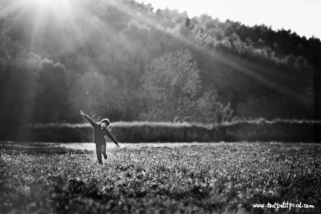 backlit picture of child running in a field by Lisa Tichane 3