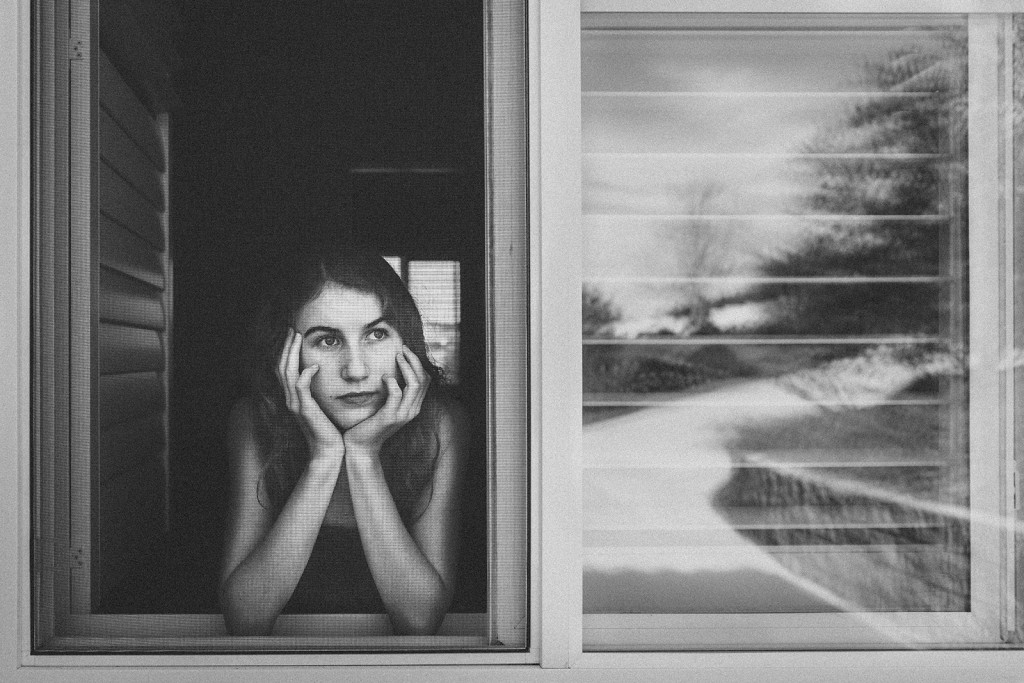 black and white photo of teen girl looking out a window by Tammy Wahl