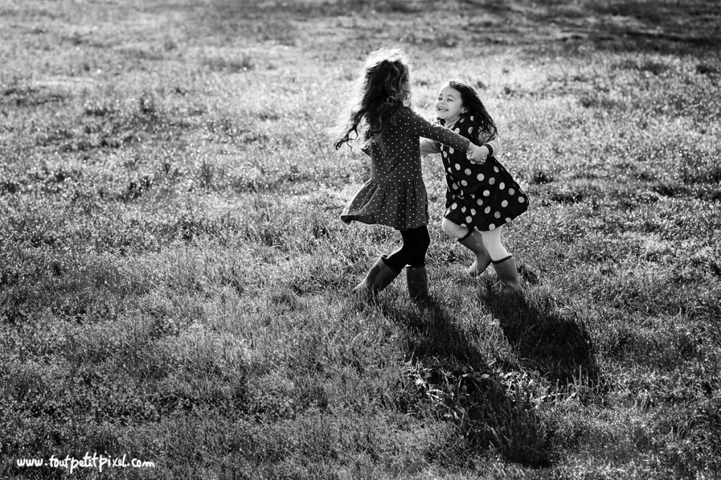 black and white photo of two girls twirling in a field by Lisa Tichane 0