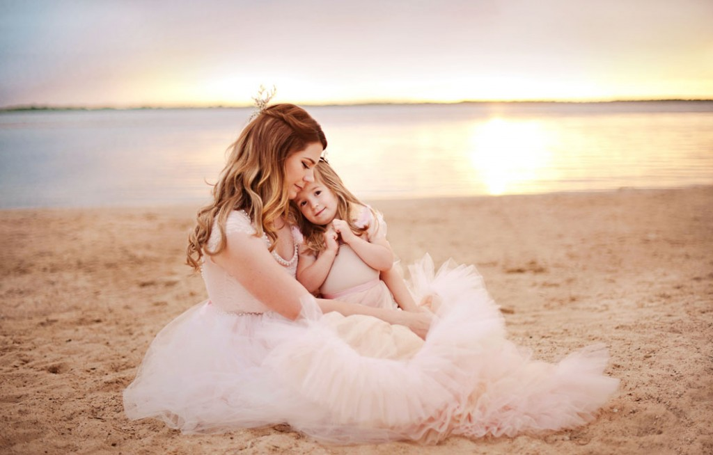 girl sitting on moms lap on the beach by Woodsy Wonders Photography