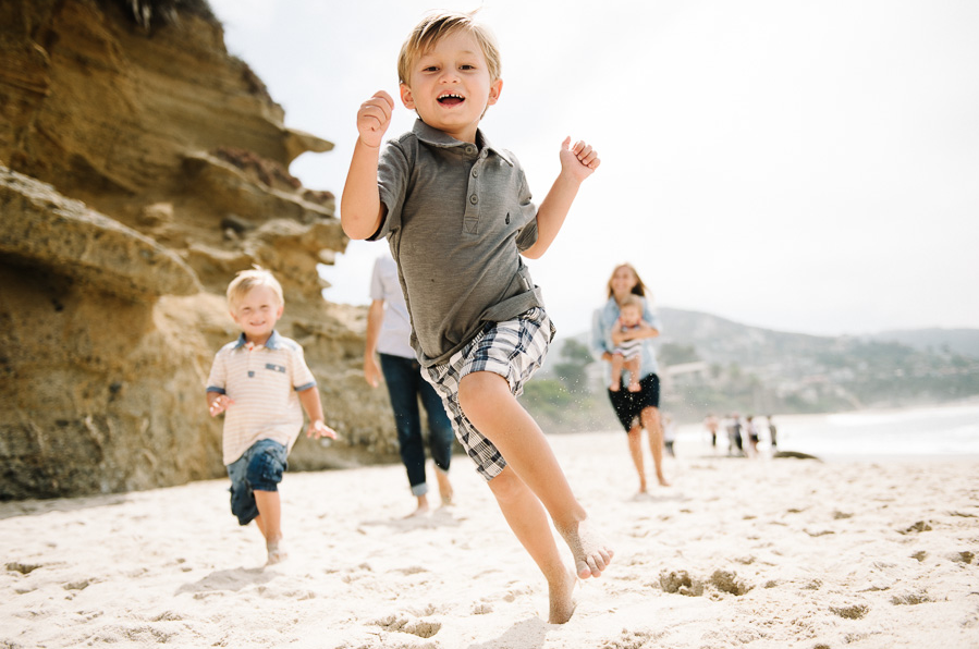 photo of boy skipping on the beach with his family by Jen J Photography