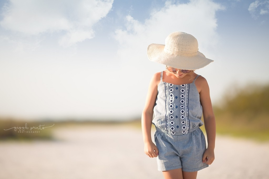 photo of girl in a sunhat on the beach by Marcie Reif