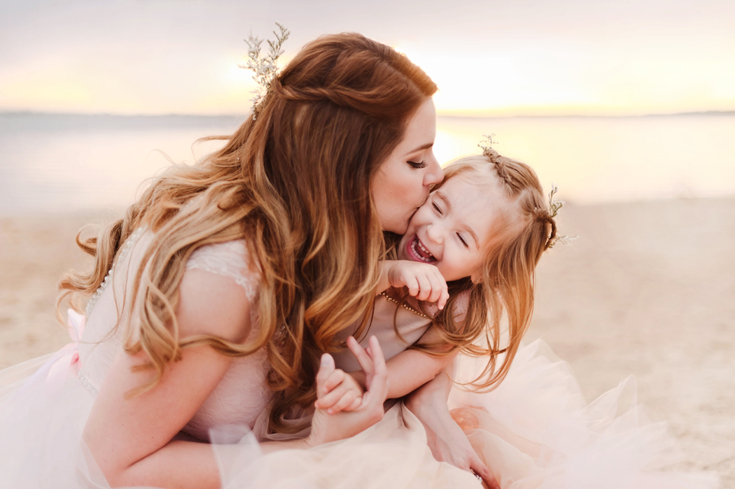 photo of mom giving daughter a kiss on the beach by Woodsy Wonders Photography
