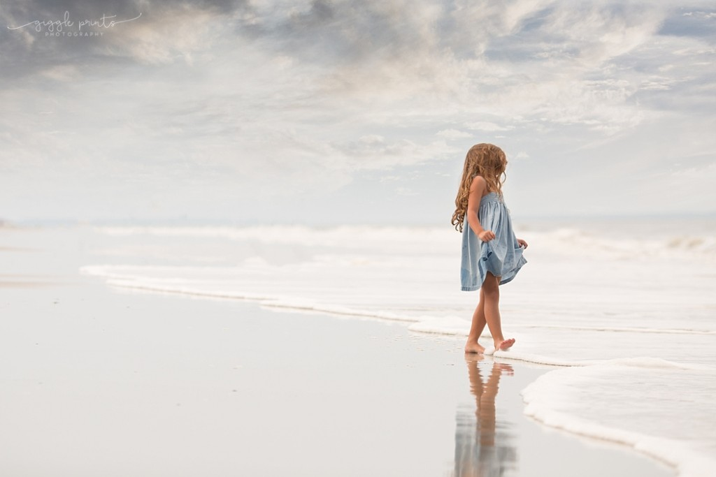 picture of girl in a blue dress walking along the water on the beach by Marcie Reif