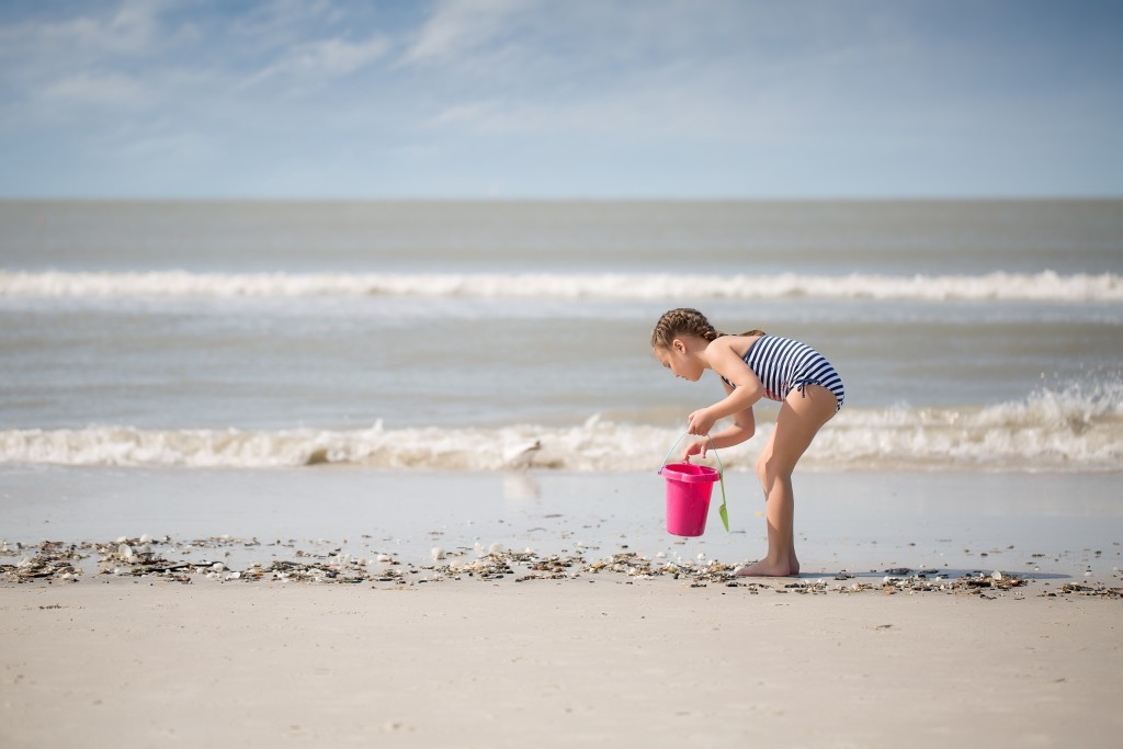 picture of girl picking up seashells on the beach by Marcie Reif