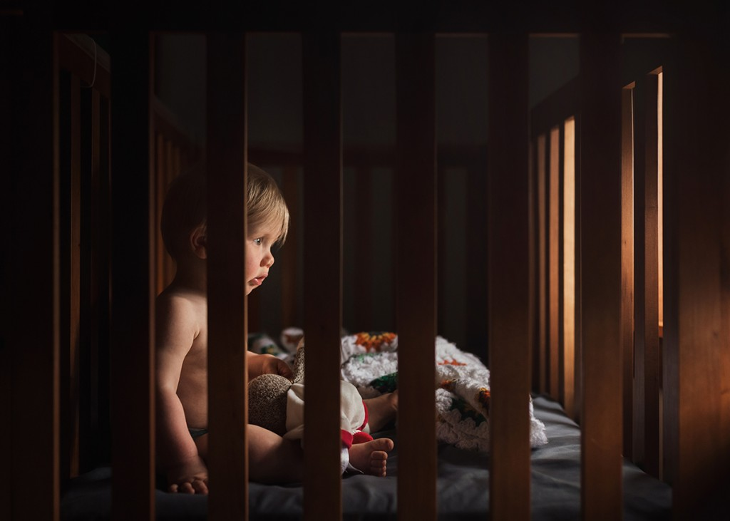 picture of toddler sitting in his crib with a sock monkey doll by Meg Loeks Photography
