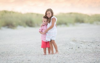 portrait of brother and sister on the beach by Marcie Reif