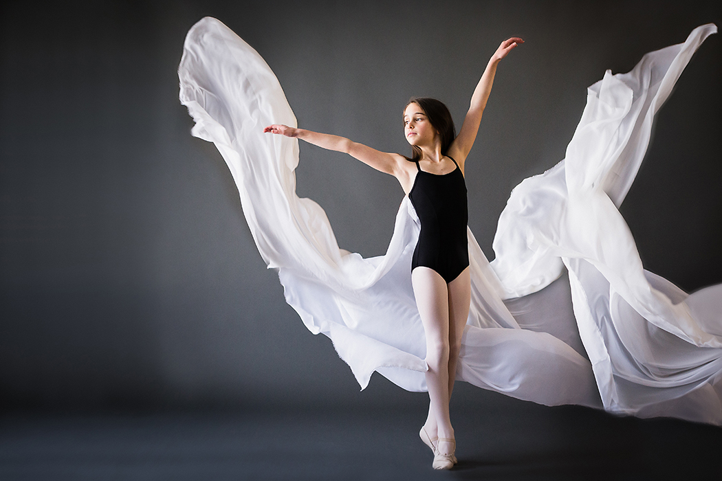 portrait of young girl dancing with white fabric flowing in the air by Faye Sevel