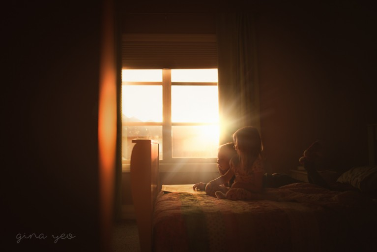 backlight photo of two girls reading on a bed by Gina Yeo