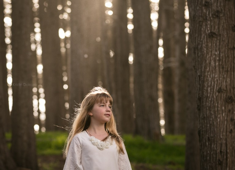 backlit photo of young girl by Kristin Dokoza