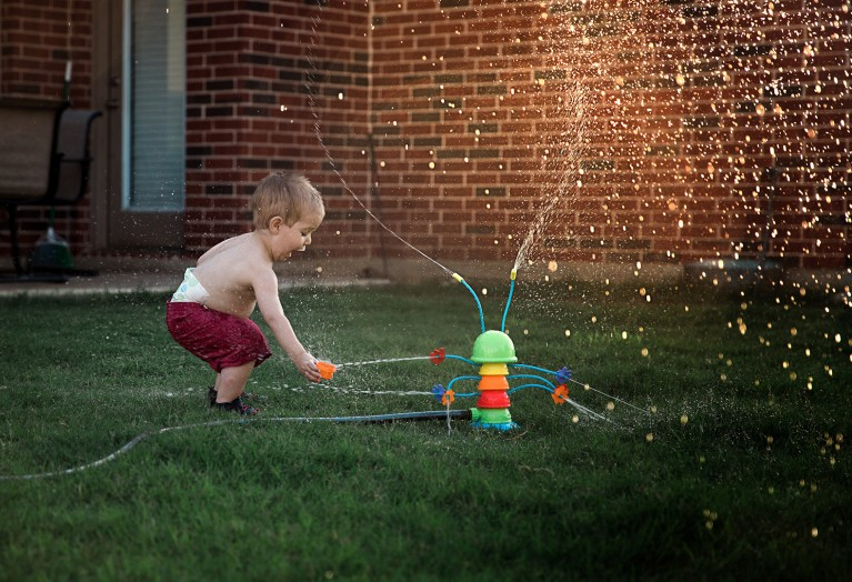 backlit pic of boy playing in a water sprinkler by Kimberly Milano