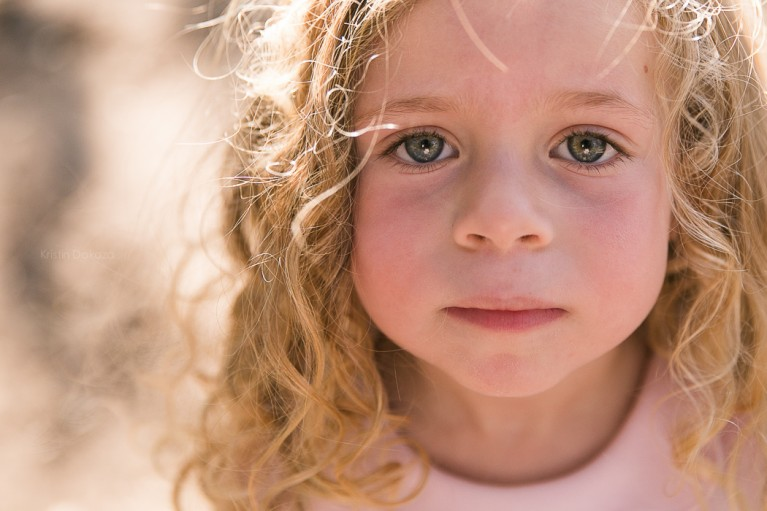 close up photo of young girl with curly hair by Kristin Dokoza