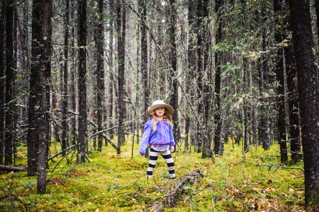 girl standing in the middle of a forrest with a hat on by Charlaine Williams