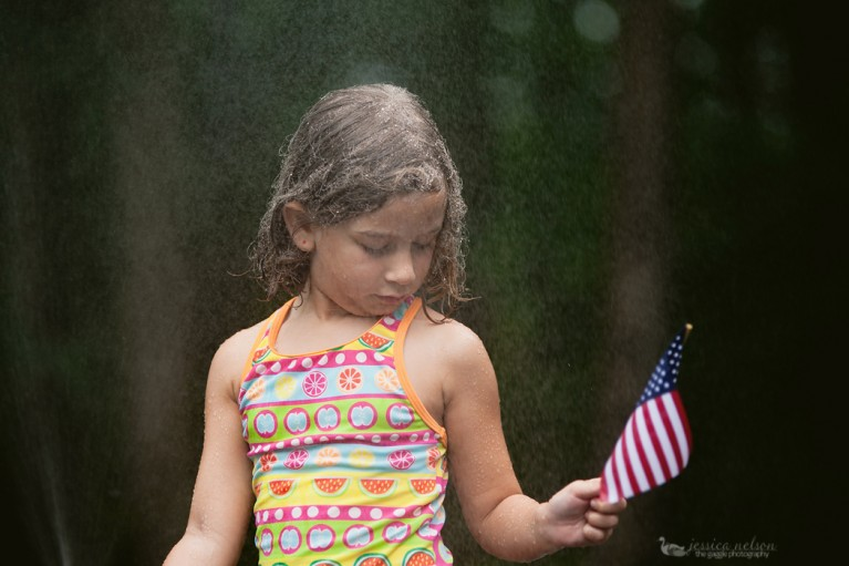 girl standing in the sprinkler water holding an American flag by Jessica Nelson