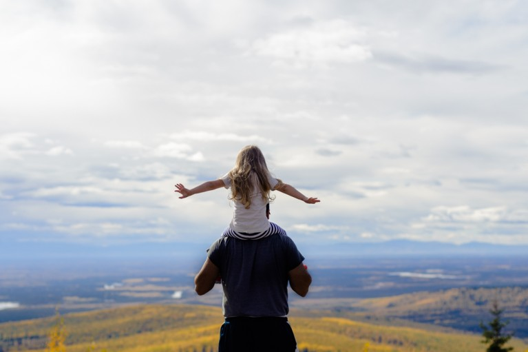 photo of girl sitting on dads shoulders outside by Charlaine Williams