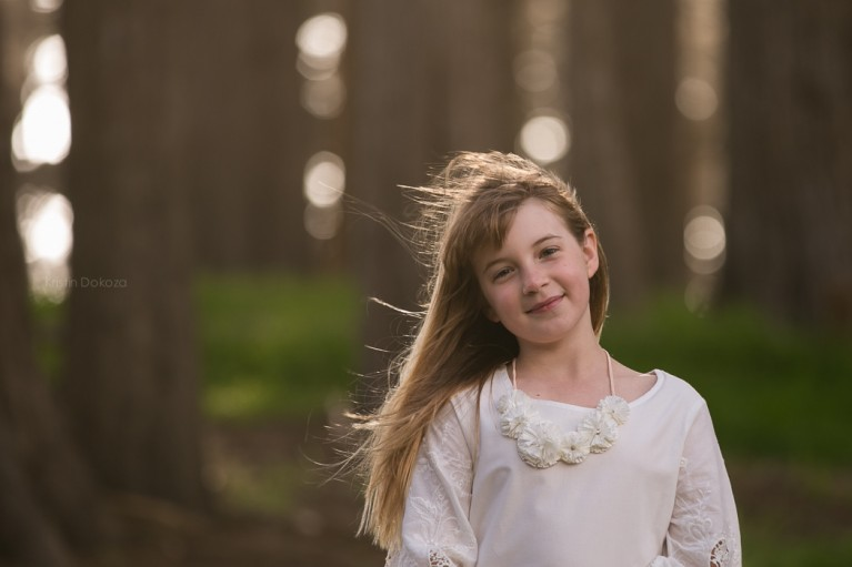 picture of girl smiling near trees by Kristin Dokoza
