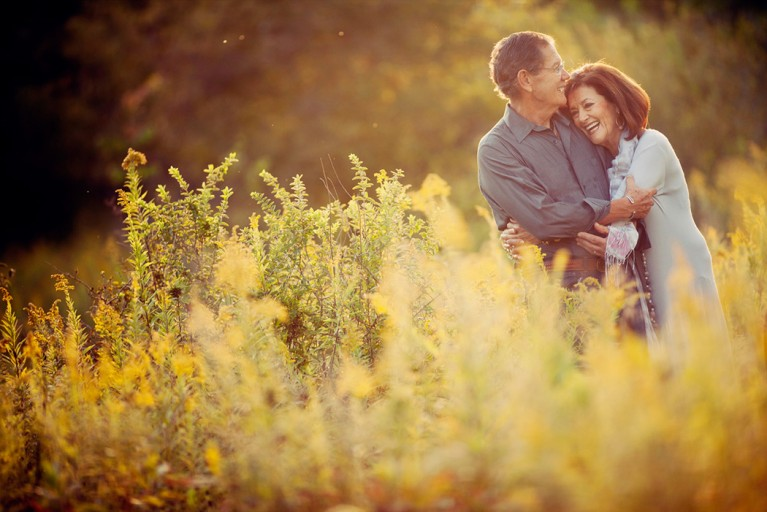 picture of man and woman hugging and laughing in a field by Julia Woods