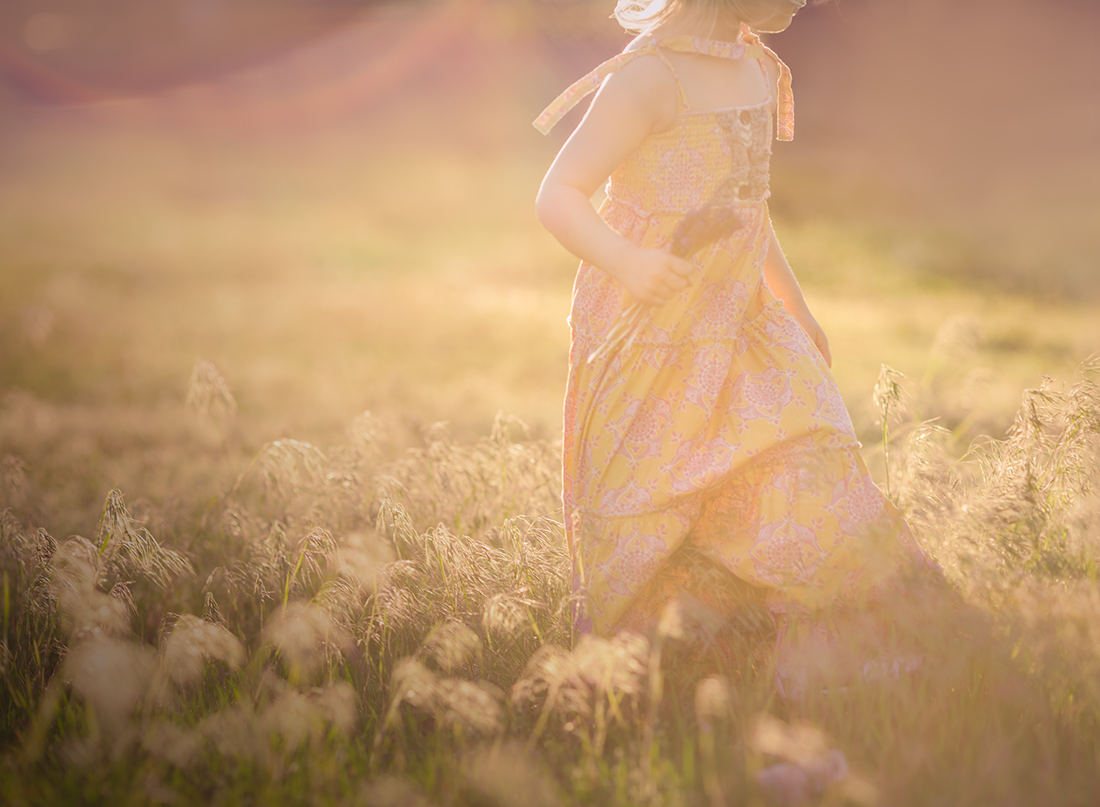 backlit photo of girl in a dress holding flowers by Kate Luber