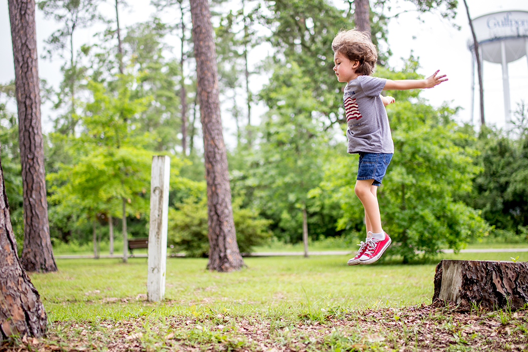 boy jumping off a tree stump by Jamie Campfield Bates