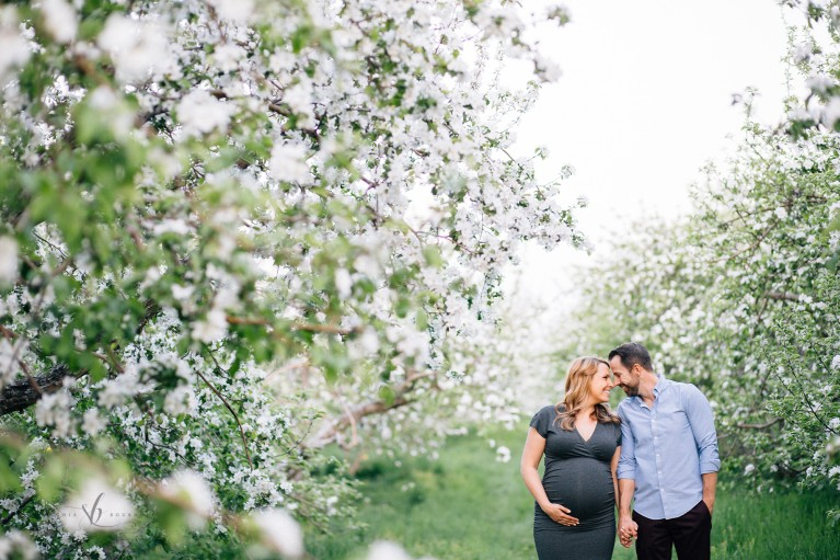 maternity portrait of man and woman standing near rows of blooming trees by Sonia Bourdon