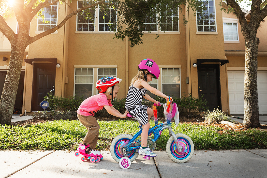 photo of brother pushing sister on bicycle by Jennifer Kielich