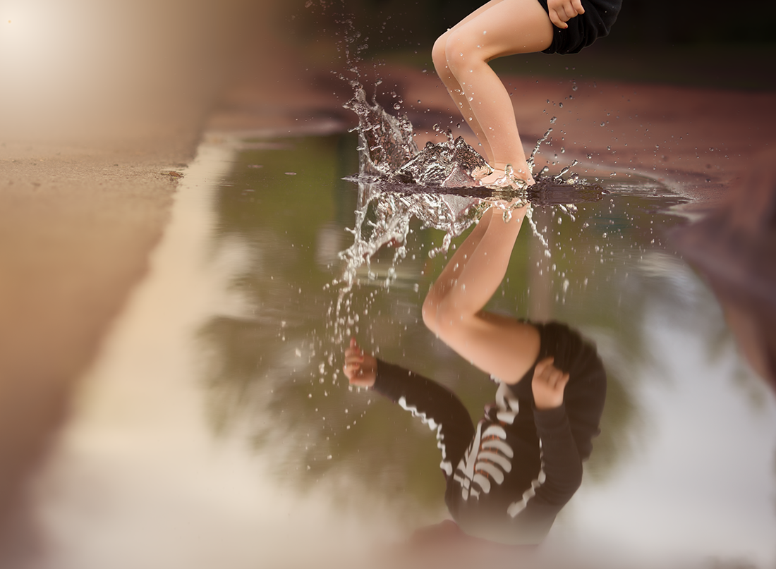photo of kid jumping in a puddle of water by Kate Luber