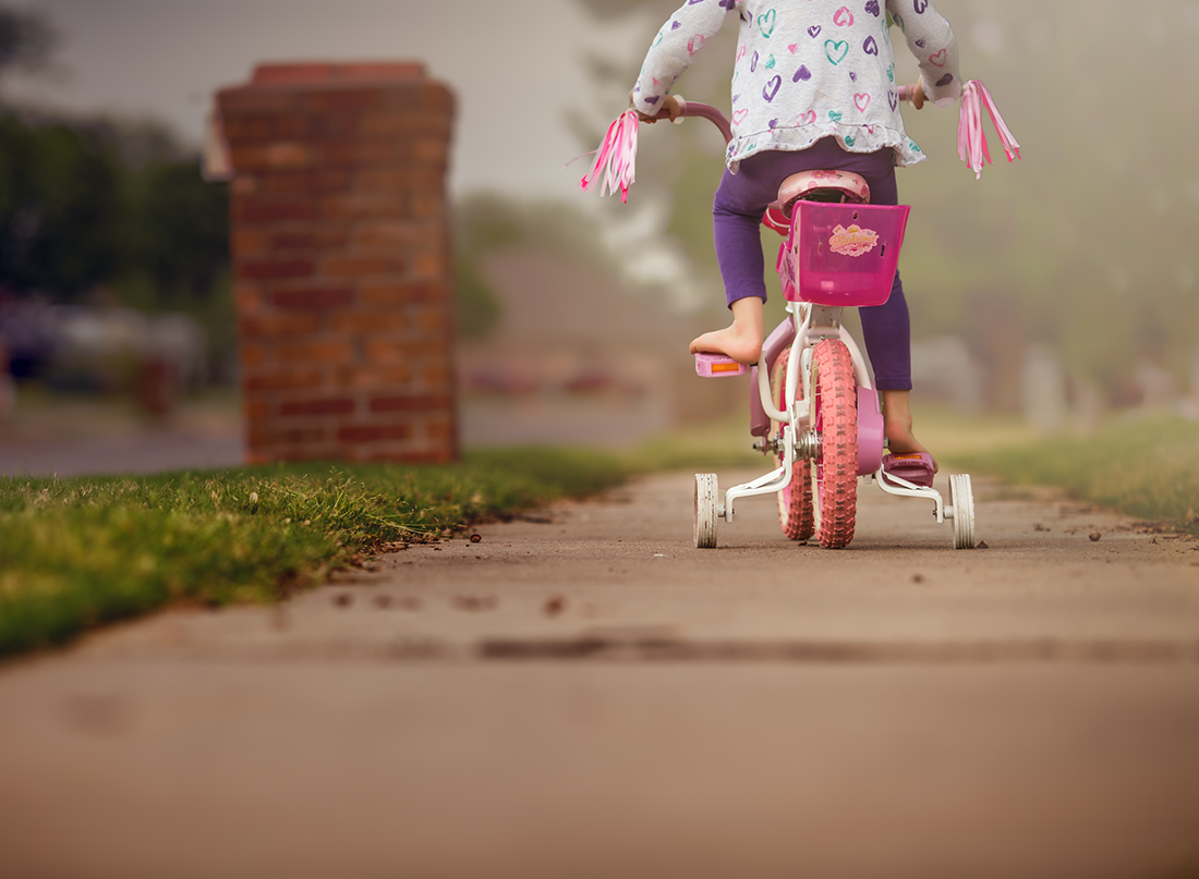 photo of kid riding a bike down the sidewalk by Kate Luber