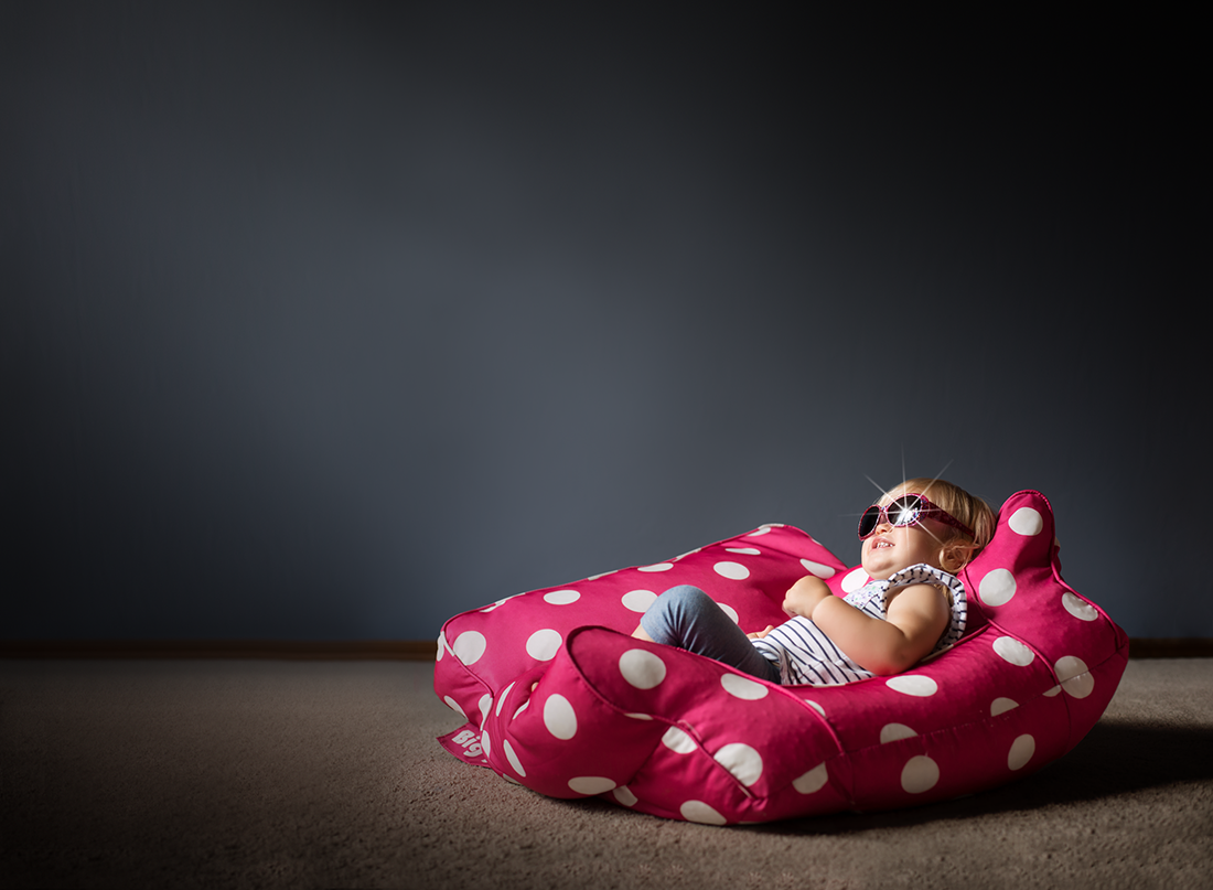 photo of kid with sunglasses on laying on a beanbag by Kate Luber