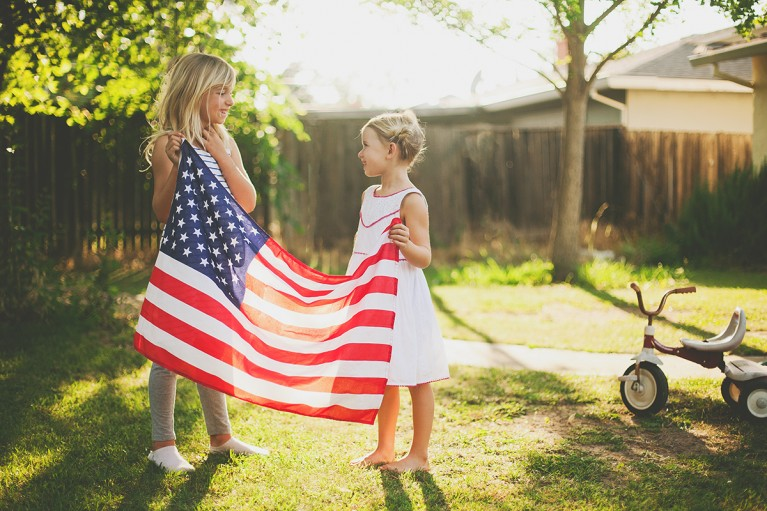 photo of two girls holding an American flag by Heather Lazark
