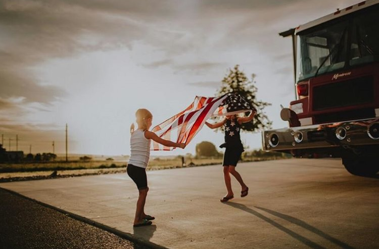 photo of two girls holding an American flag
