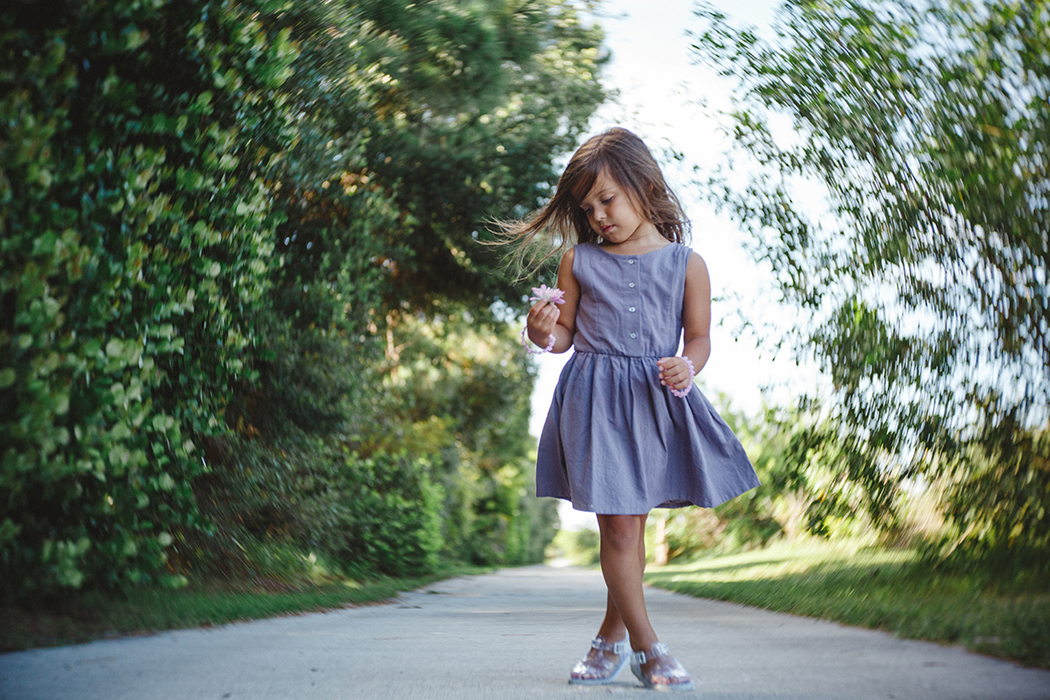 picture of a girl holding a flower by Carolina Gonzalez