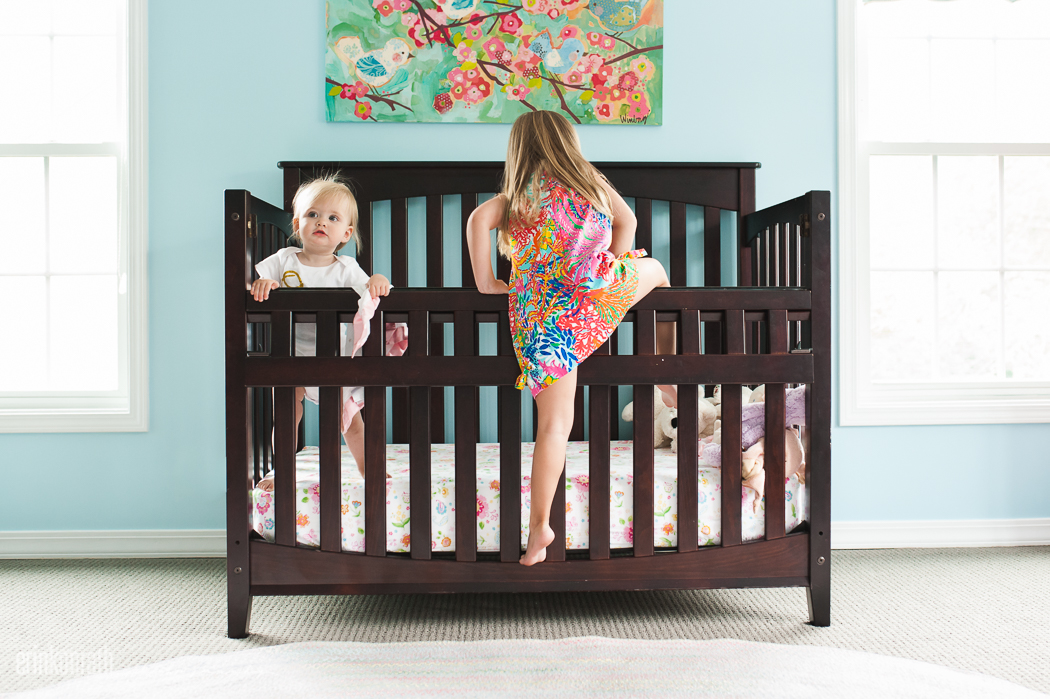 picture of girl climbing into crib with sibling by Erin Konrath