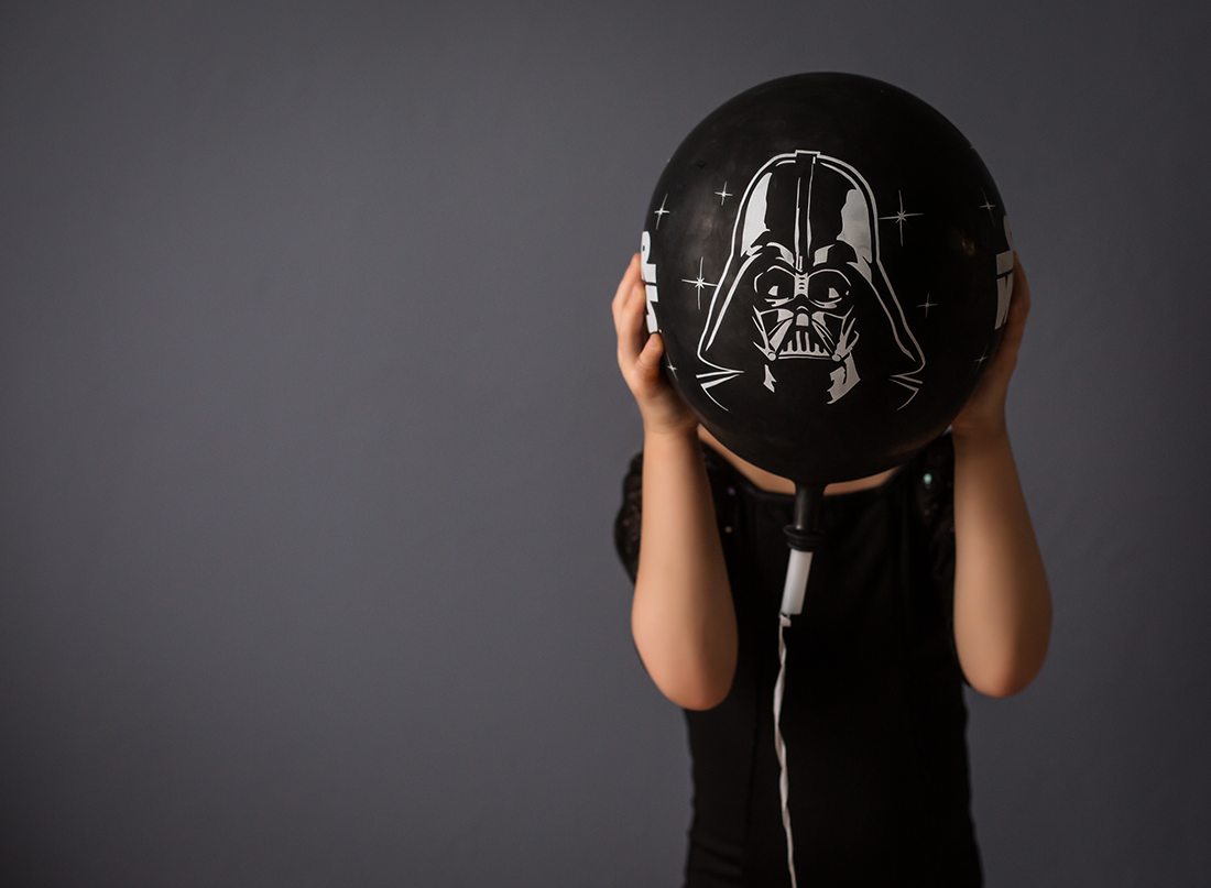 picture of girl holding a Darth Vader balloon by Kate Luber