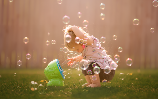 picture of girl playing in a bubble machine by Kate Luber