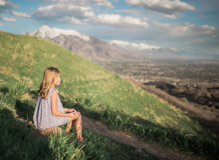 picture of girl sitting on a rock by the mountains by Carly Bingham