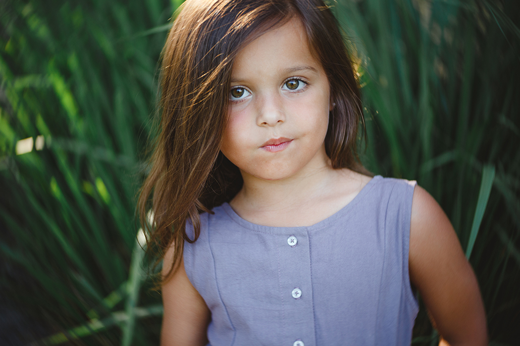 portait of young girl in front of green grass by Carolina Gonzalez