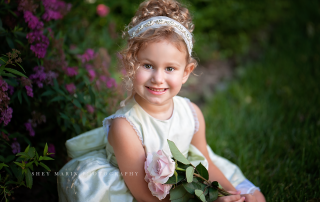 portrait of girl sitting and smiling while holding flowers by Shey Detterline