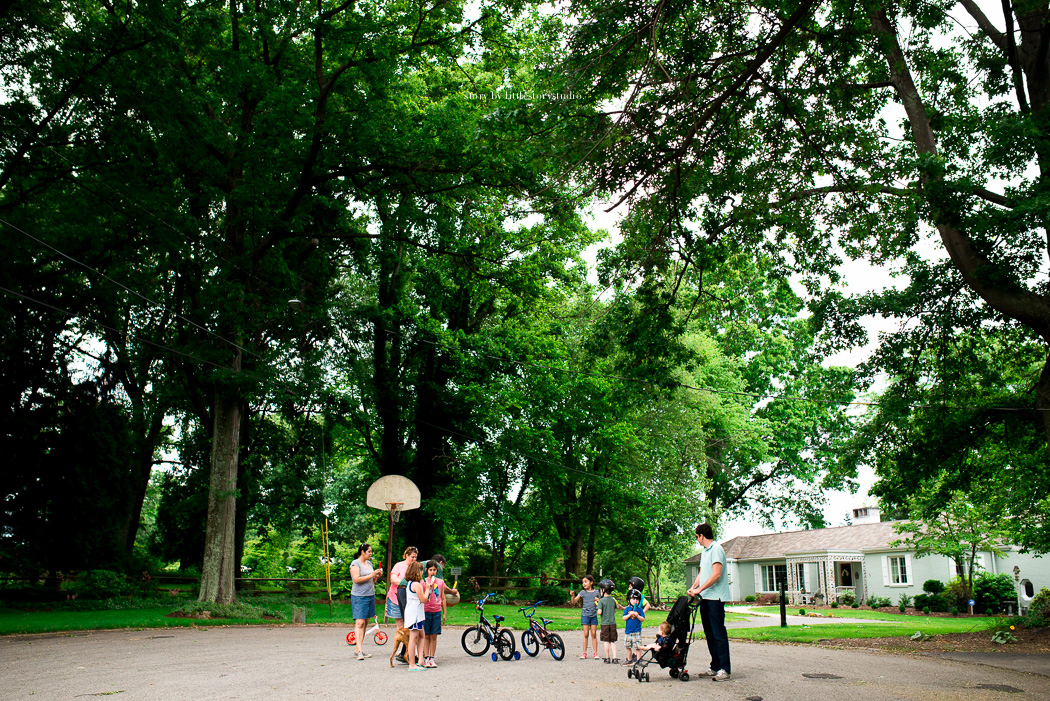 wide angle photo of people playing and riding bikes in a driveway by Andrea Moffatt