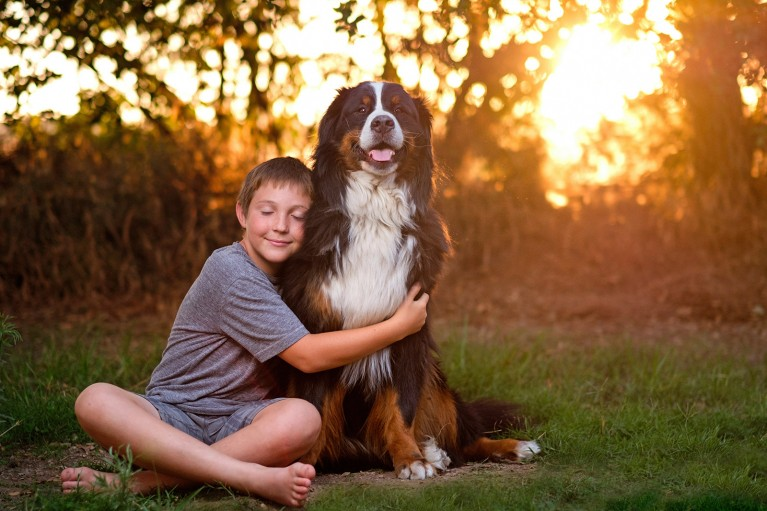 backlit photo of boy hugging his dog by Michelle Turner