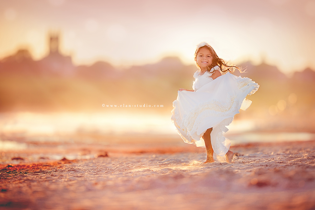 girl holding her dress while she twirls by Tracy Sweeney of Elan Studio