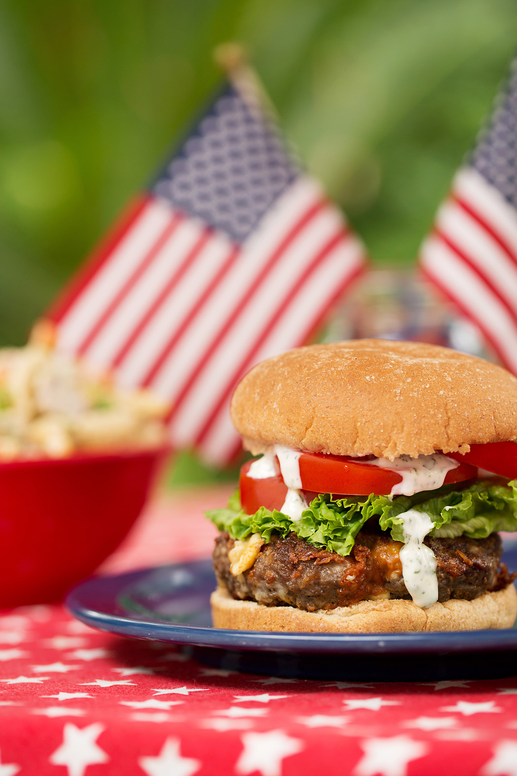 photo of a juicy burger with American flags by Elizabeth Gelineau