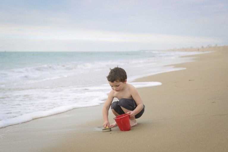 photo of boy digging up sand on the beach by Karyn Olsson