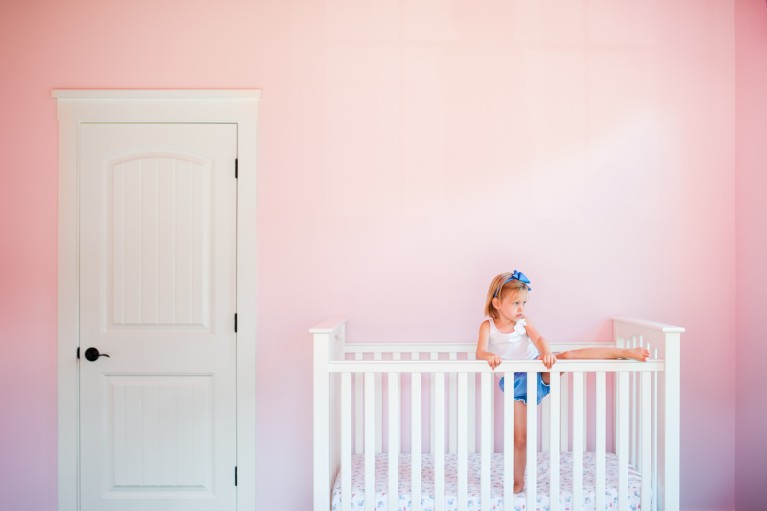 photo of girl climbing out of a crib in a pink room by Erin Konrath