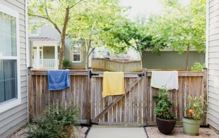 photo of towels drying over a fence by Ashley Maple