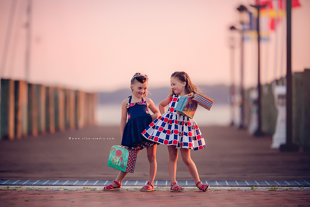 picture of twins on a dock with suitcases by Tracy Sweeney of Elan Studio