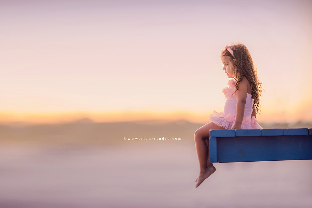 picture of young girl sitting on a blue dock by Tracy Sweeney of Elan Studio