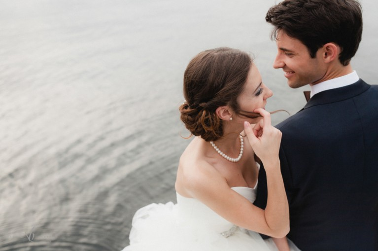 bride and groom sitting by the water by Sonia Bourdon